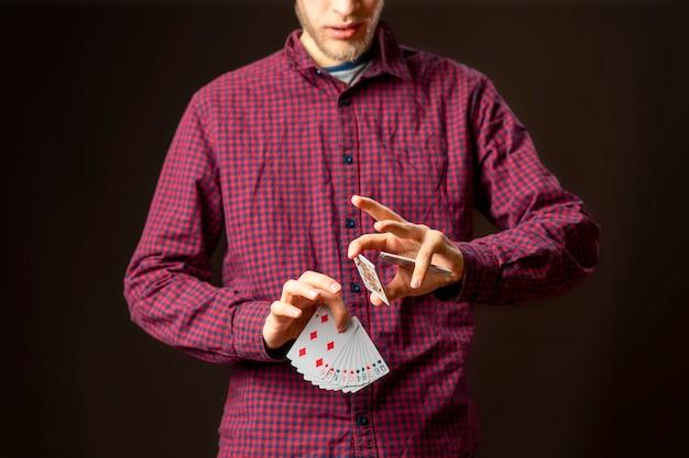 Портрет крупным планом подростка мужского пола, держащего игровую карту, показывает его и прикрывает лицо b
