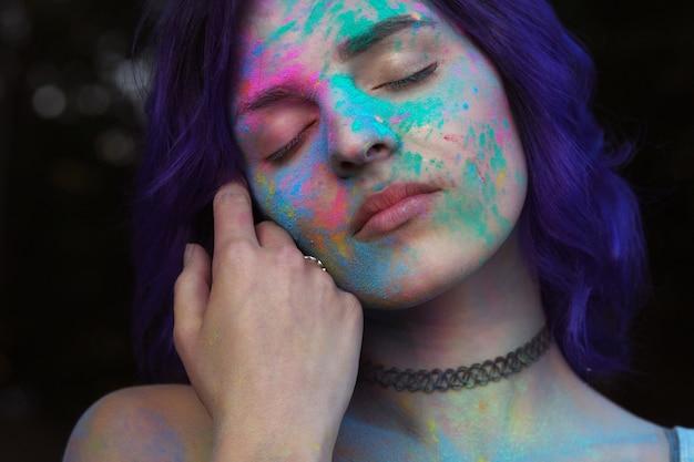 カラフルなガラルパウダーで覆われた紫色の髪を持つ優しい若い女性のクローズアップの肖像画