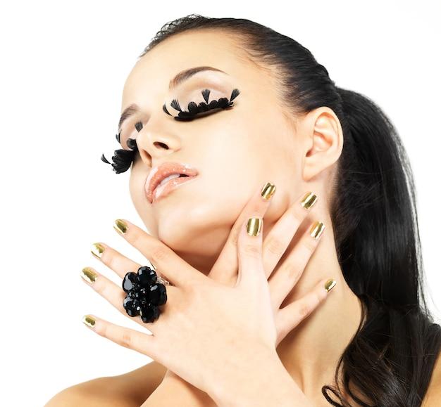 長い黒のつけまつげメイクと金色の爪を持つ美しい女性のクローズアップの肖像画。白い壁に分離