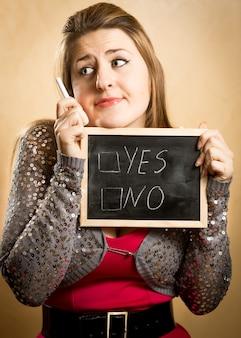 はいといいえのオプションで黒板を保持している思いやりのある女性のクローズ アップの肖像画