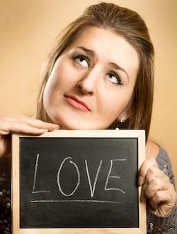 Крупным планом портрет вдумчивой женщины, держащей слово «любовь», написанное на доске