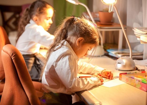 Портрет крупным планом двух маленьких школьниц, сидящих за столом и рисующих картинки