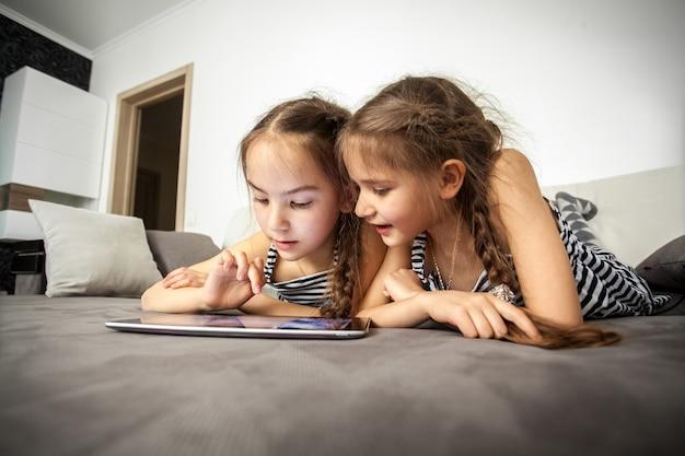 Портрет крупным планом двух сестер, лежащих на кровати с планшетом