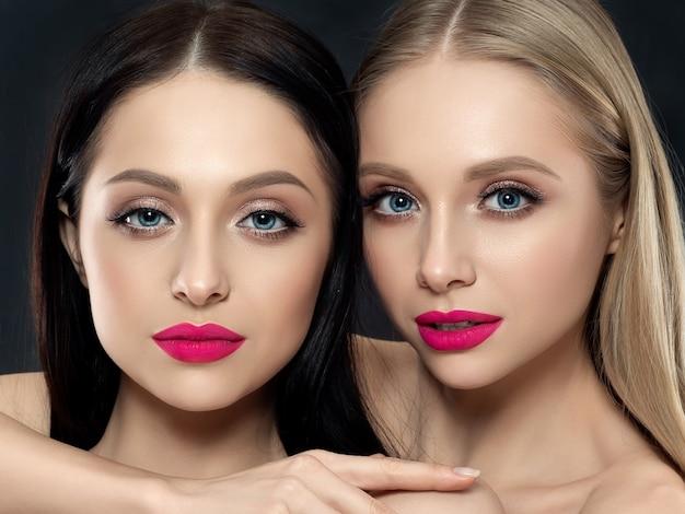 검은 벽에 두 젊은 아름 다운 여자의 근접 촬영 초상화. 밝은 분홍색 립스틱. 스킨 케어, 화장품, 스파 요법 또는 미용 개념