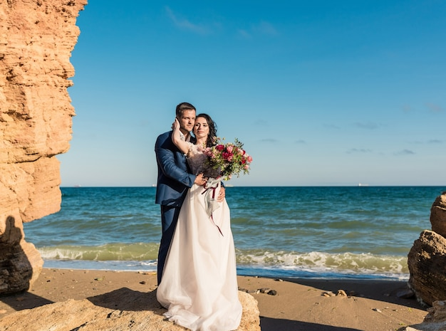 古い大聖堂でポーズをとる花束と結婚式の若い新郎新婦のクローズアップの肖像画。結婚式の日にキスする新婚旅行のカップル、恋に幸せなカップル、結婚式のキス