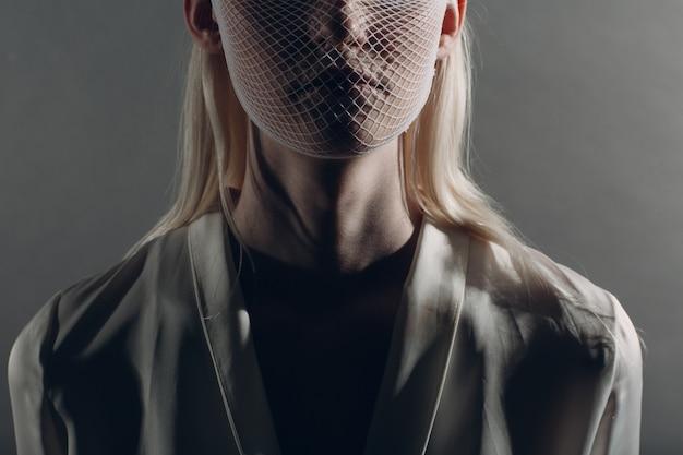 Портрет крупного плана белой кавказской фотомодели белокурой женщины альбиноса нося сетку грубой сетки карантинной медицинской маски на серой предпосылке. концепция защиты от коронавируса covid-19
