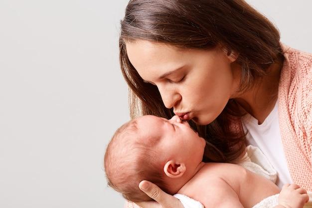 目を閉じて生まれたばかりの赤ちゃんにキスする魅力的な女性のクローズアップの肖像画