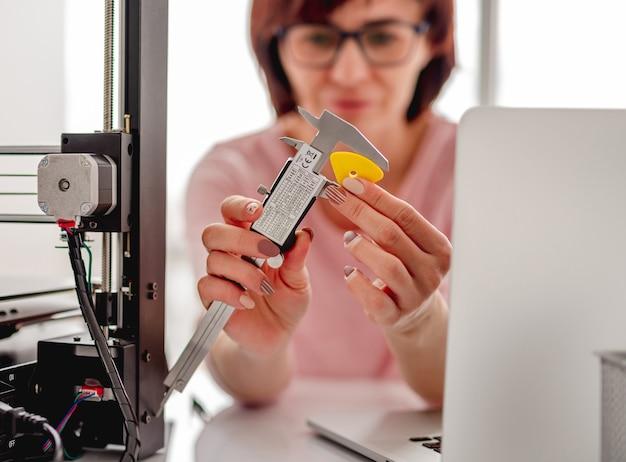 3d 프린터로 만든 플라스틱 세부 사항을 측정하는 여자의 근접 촬영 초상화