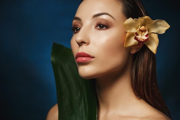 なめらかな背中の髪、耳の後ろに柔らかいユリの花を持つ女性のポートレート、クローズアップ。よそ見。美容コンセプト。