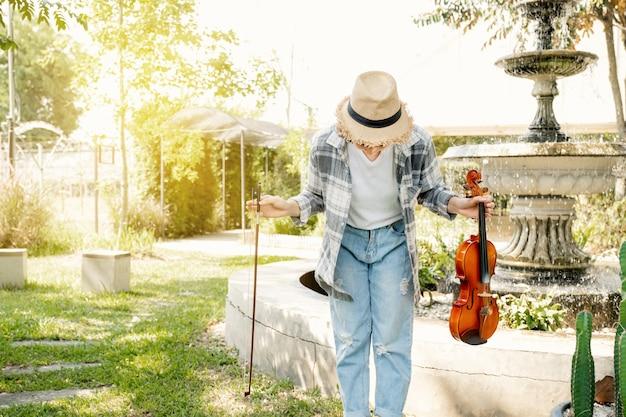 젊은 아시아 여성 음악 바이올리니스트 활의 클로즈업 초상화는 바이올린 연주 후 정원에서 휴식을 취합니다.