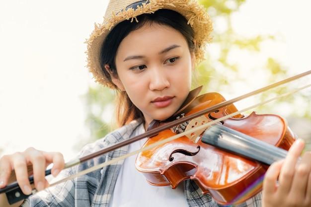 젊은 아시아 여성 음악 바이올리니스트의 근접 촬영 초상화 바이올린 연주 정원에서 휴식