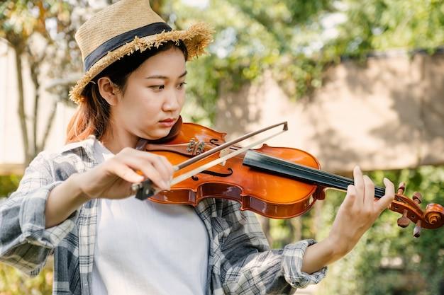 젊은 아시아 여성 음악 바이올리니스트의 클로즈업 초상화는 정원에서 바이올린을 연주하며 휴식을 취합니다.