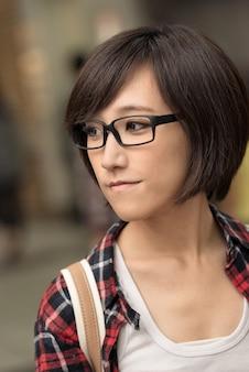 平和と青いスタンドで屋外通りを探している若いアジアの女性のクローズアップの肖像画。