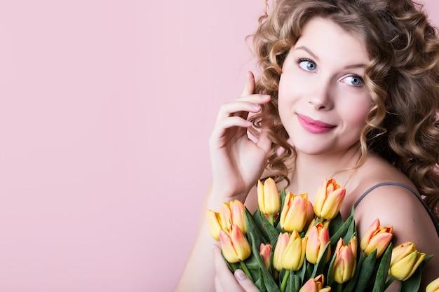 Портрет крупного плана молодой красивой белокурой девушки с букетом тюльпанов на розовом.