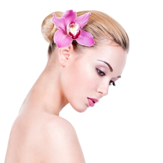 顔の近くに花を持つ若い美しい少女のクローズアップの肖像画-白い壁に分離