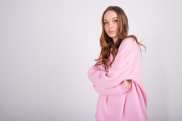 Портрет крупного плана молодой красивой усмехаясь женщины смотря камеру. модная девушка в повседневной розовой толстовке с капюшоном.