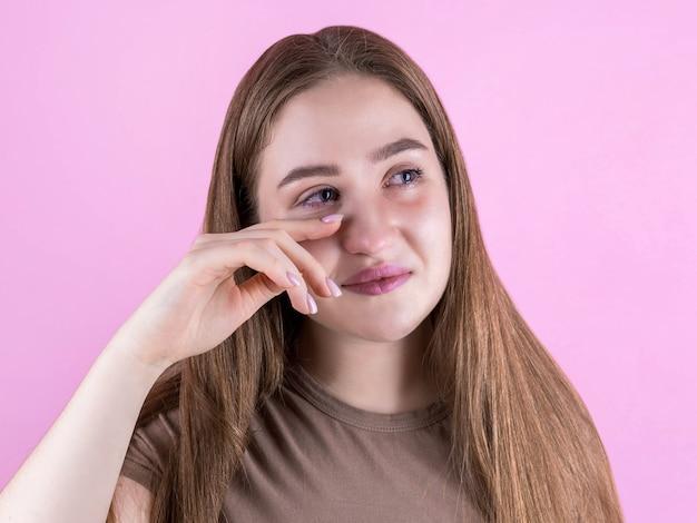 Портрет крупным планом молодой красивой женщины, плачущей изолированной на розовом, вытирает слезы, глядя в камеру
