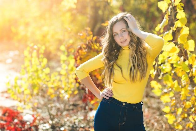 Портрет крупного плана молодой красивой женщины на осени. стильная привлекательная женщина в осеннее время. блондинка с вьющимися волосами.