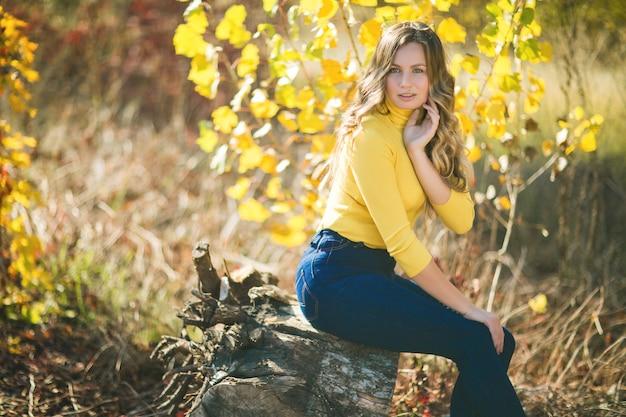 秋の若い美しい女性のポートレート、クローズアップ。秋のスタイリッシュな魅力的な女性。巻き毛の金髪の女性。