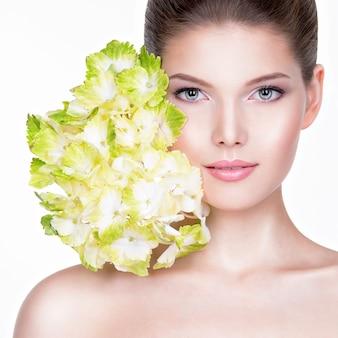 健康できれいな肌を持つ若い美しい女性のクローズアップの肖像画-白い背景で隔離。