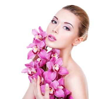 Портрет крупного плана молодой красивой женщины со здоровой чистой кожей лица. довольно взрослая девушка с цветком у лица. - изолированные на белом фоне