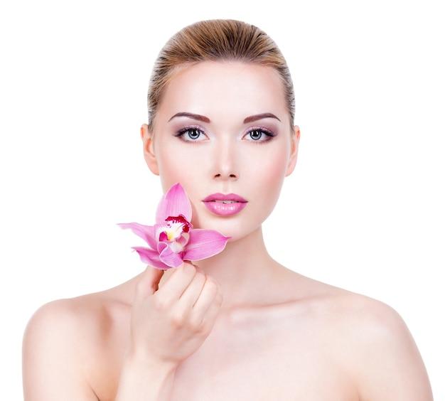 顔の健康的なきれいな肌を持つ若い美しい女性のクローズアップの肖像画。顔の近くに花を持つかなり大人の女の子。 -白い壁に隔離