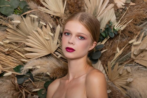 얼굴의 건강한 피부를 가진 젊은 아름 다운 여자의 근접 촬영 초상화. 봄 마른 필드 꽃의 배경에 부르고뉴 입술을 가진 금발 소녀. 아름다움 얼굴 관리 개념입니다.