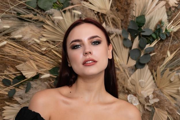 얼굴의 건강한 피부를 가진 젊은 아름 다운 여자의 근접 촬영 초상화. 봄 마른 필드 꽃의 배경에 부르고뉴 입술을 가진 아름 다운 갈색 머리 소녀. 열린 어깨