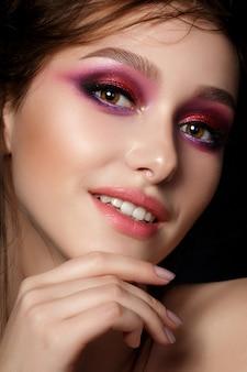 明るいピンクのスモーキーな目と唇を持つ若い美しい女性のクローズアップの肖像画。ファッションメイク。現代の夏のメイクアップ