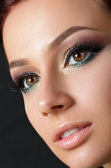 夕方のメイクアップと若い美しい女性のクローズアップの肖像画。モデルのポーズ。アイライナー付きスモーキーアイ。古典的なメイクのコンセプト。