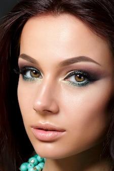夕方の若い美しい女性のクローズアップの肖像画は、青いネックレスを身に着けています。モデルのポーズ。アイライナー付きスモーキーアイ。古典的なメイクのコンセプト。