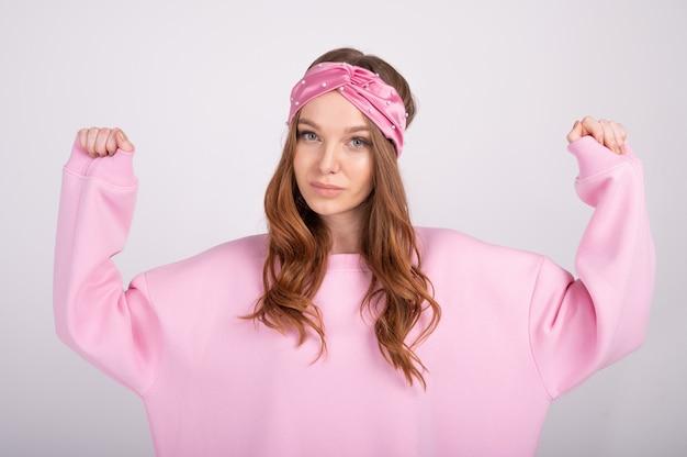 Портрет крупного плана молодой красивой женщины с поднимающимися руками. модная девушка в повседневной розовой толстовке с капюшоном.