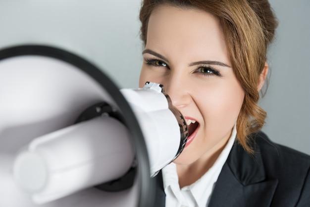 メガホンで叫んでいる若いビジネス女性のポートレート、クローズアップ