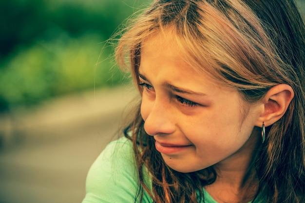 Портрет крупного плана молодой плачущей девушки со слезами. девочка-подросток с грустным выражением лица плачет.