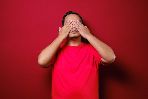 若い男、男、学生、少年、労働者、従業員、手で目を閉じて、見ることができない、隠れて、赤い背景で隔離のクローズアップの肖像画。邪悪な概念を見ないでください。人間の感情の表情