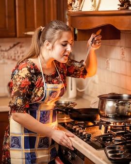 Крупным планом портрет молодой домохозяйки, дегустации супа из сковороды на огне