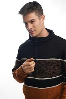 暖かい縞模様のセーターを着て、白い壁にポーズをとって若い男性のクローズ アップの肖像画
