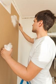 Крупным планом портрет молодого человека, выравнивающего стену с замазкой