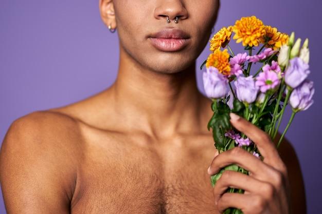 Портрет крупным планом губ молодого человека с цветами в руке, мышечной чувственной сильной латиноамериканской модели