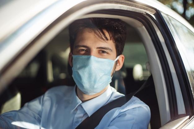 젊은 남자의 클로 우즈 업 초상화는 살 균 의료 마스크를 착용하는 차에 앉아있다. 사회적 거리, 바이러스 확산 방지 및 치료 개념.