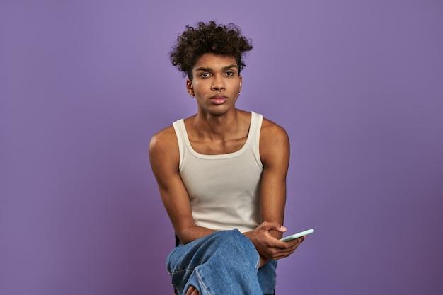 젊은 남자의 클로 우즈 업 초상화는 모바일 및 격리 된 보라색 배경에 카메라를 찾고 앉아