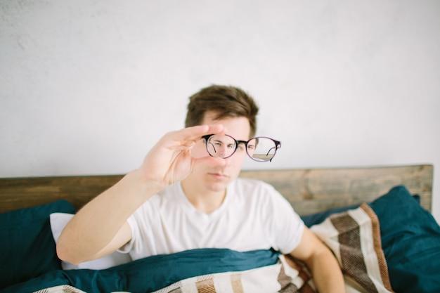 Портрет крупного плана молодого человека в очках. у него проблемы со зрением, он немного прищуривается