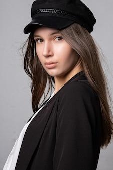 若いモデルのクローズアップの肖像画は、灰色のスタジオの背景でポーズをとってキャップとジャケットを着ています