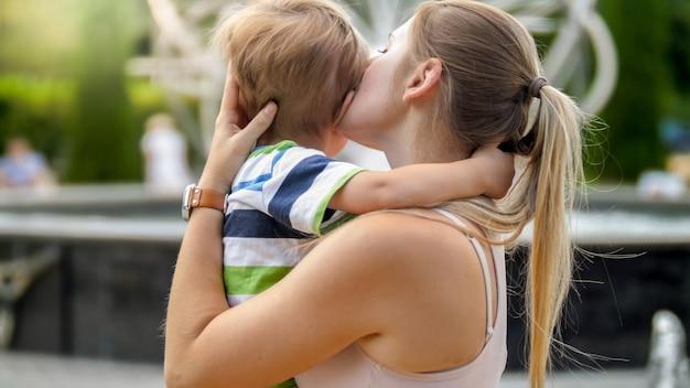 公園で泣いている小さな男の子を抱き締めると愛撫する若い母親のポートレート、クローズ アップ