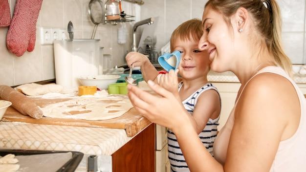 쿠키를 만드는 그녀의 유아 아들을 가르치는 젊은 어머니의 클로 우즈 업 초상화. 집 부엌에서 베이킹 팬에 부모 베이킹 디저트와 아이