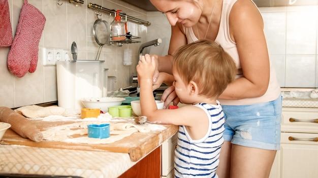쿠키를 만드는 그녀의 유아 아들을 가르치는 젊은 어머니의 근접 촬영 초상화
