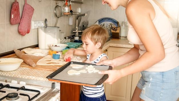 베이킹 팬을 들고 부엌에서 쿠키를 만드는 유아 소년과 젊은 어머니의 근접 촬영 초상화