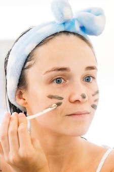 얼굴 정화 및 스파 치료를 위해 커피 마스크를 적용하는 젊은 여성의 클로우즈업 초상화