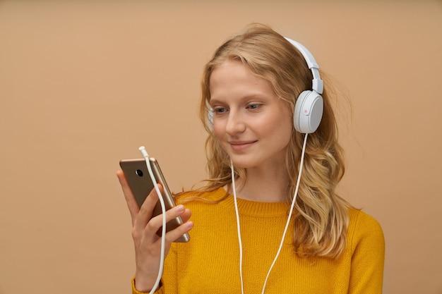 헤드폰을 통해 젊은여자가 듣는 음악의 근접 촬영 초상화
