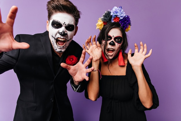 恐ろしい顔でポーズをとる男性と女性のハロウィーンのクローズアップの肖像画。赤いディテールが叫んでいる黒い服を着たカップル。